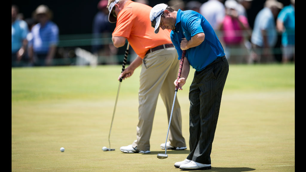 Tim Clark (R) of South Africa uses an anchored putter during practice before the US Open at Merion Golf Club on June 12, 2013 in Ardmore, Pennsylvania. AFP PHOTO/Brendan SMIALOWSKI