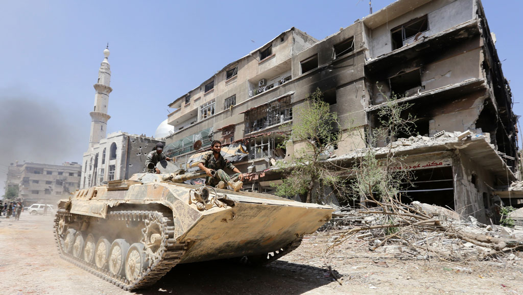 THIS PICTURE WAS TAKEN ON A GOVERNMENT-GUIDED TOUR Syrian government troops sit atop a tank as they drive past a damaged building in Mleiha on the outskirts of the capital Damascus on August 15, 2014. Syrian government forces retook the key town southeast of the capital on August 14, after a months-long battle against rebels, a military source and state television said. AFP PHOTO/LOUAI BESHARA (Photo credit should read LOUAI BESHARA/AFP/Getty Images)
