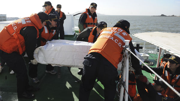 In this photo released by the Korea Coast Guard, members of the Korea Coast Guard carry the body of a civilian killed in Tuesday's bombardment by North Korea.